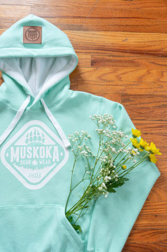 Mint coloured Ladies Sherpa Hoody from Muskoka Bear Wear laying on a wooden floor with babys breath and daisys sticking out of the middle pocket.