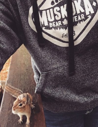 Close-up of a woman wearing a Muskoka Bear Wear hoody and a chipmunk peeking out from under her arm
