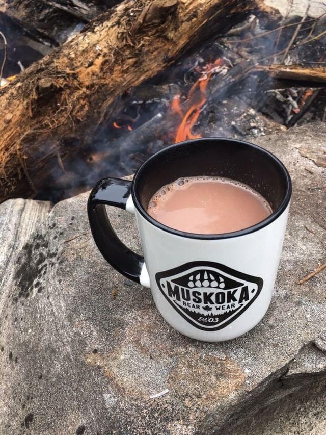 Muskoka Bear Wear coffee cup beside the fire
