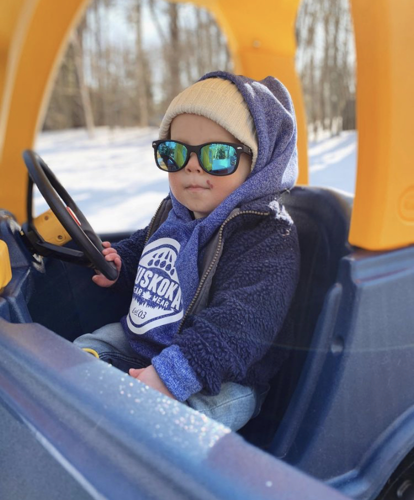 Toddler wearing a Muskoka Bear Wear hoody and some sunglasses while driving a play car