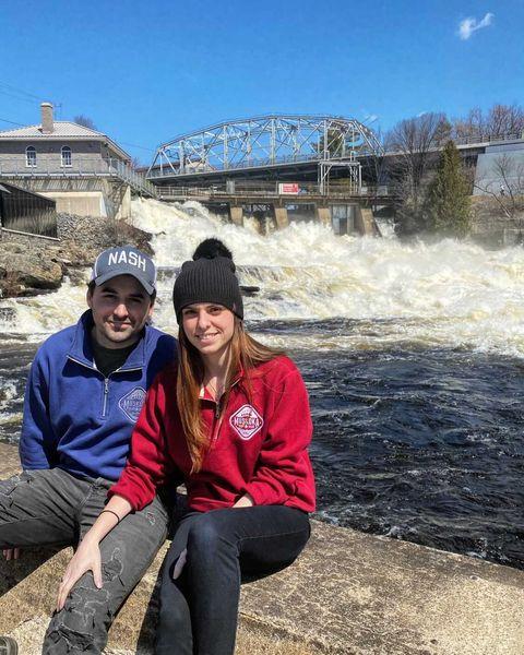 Canadian Couple sitting on rock in front of a waterfall wearing a Muskoka Bear Wear quarter zip sweaters