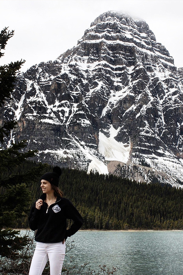 Canadian Woman standing in front of Banff mountains and lake wearing a black MBW quarter-zip sweater and white jeans