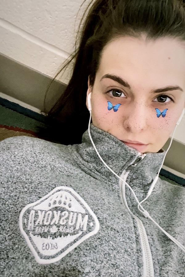 Canadian girl wearing a heather grey quarter zip Muskoka Bear Wear sweater listening to something with headphones