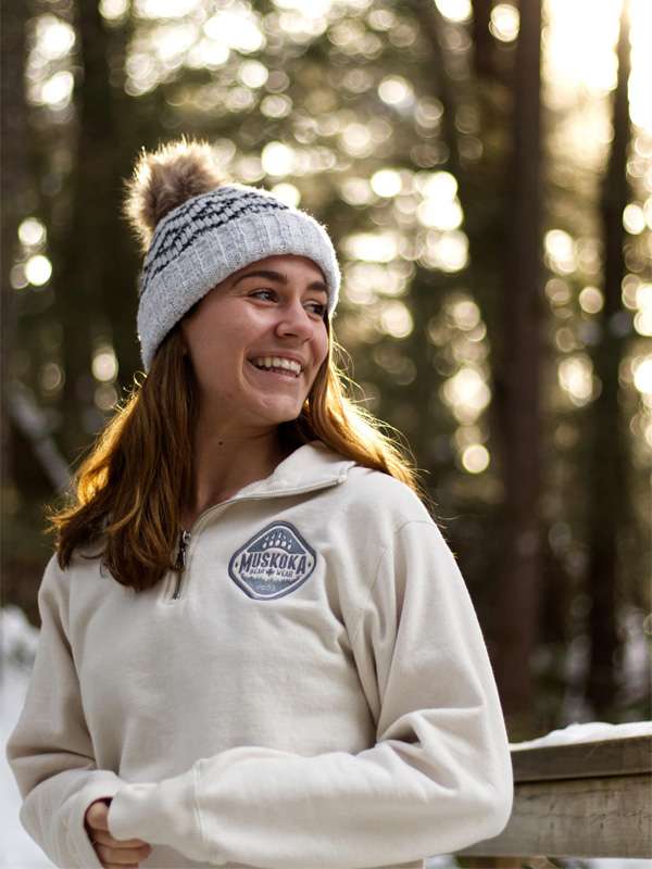 Canadian woman looking off to the side, standing in a forest, wearing a knit toque and Muskoka Bear Wear Ladies Quarter Zip