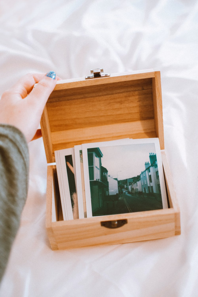 wooden box open with old polaroids inside.