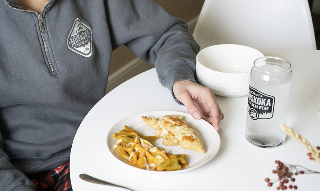 Close-up of person sitting at a dinner table with chicken Parmesan and pasta, a MBW glass full of water, wearing a dark grey ladies quarter-zip and red cottage comfy pants.