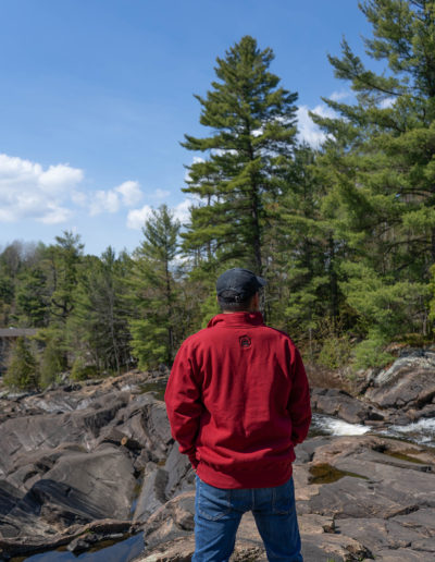 Canadian Man wearing a Cranberry Red Muskoka Bear Wear Men's Quarter Zip, standing on rocks looking out a the forest