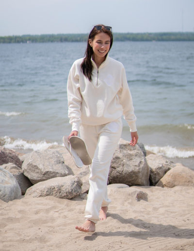 Canadian Influencer Em Rowsell wearing a Muskoka Bear Wear Ivory Quarter Zip and Ivory MBW Camp Pants walking on the beach holding white flip flops