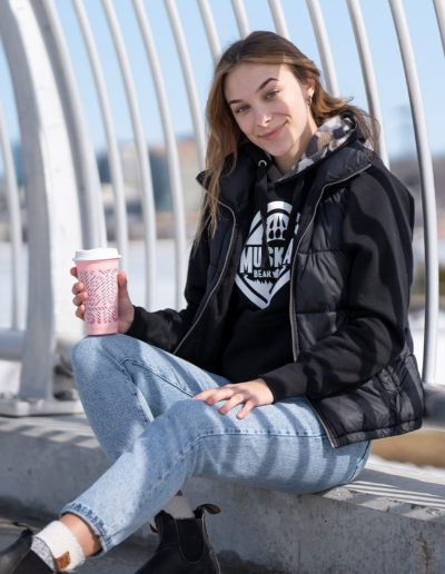 Canadian Influencer Maitland Galetzka sitting against a metal fence holding a pink coffee cup and wearing a black Muskoka Bear Wear sweater