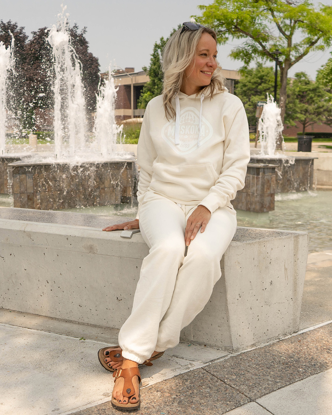 Canadian Woman sitting in front of fountain in Galt, Ontario wearing a matching Ivory sweater and sweatpants outfit