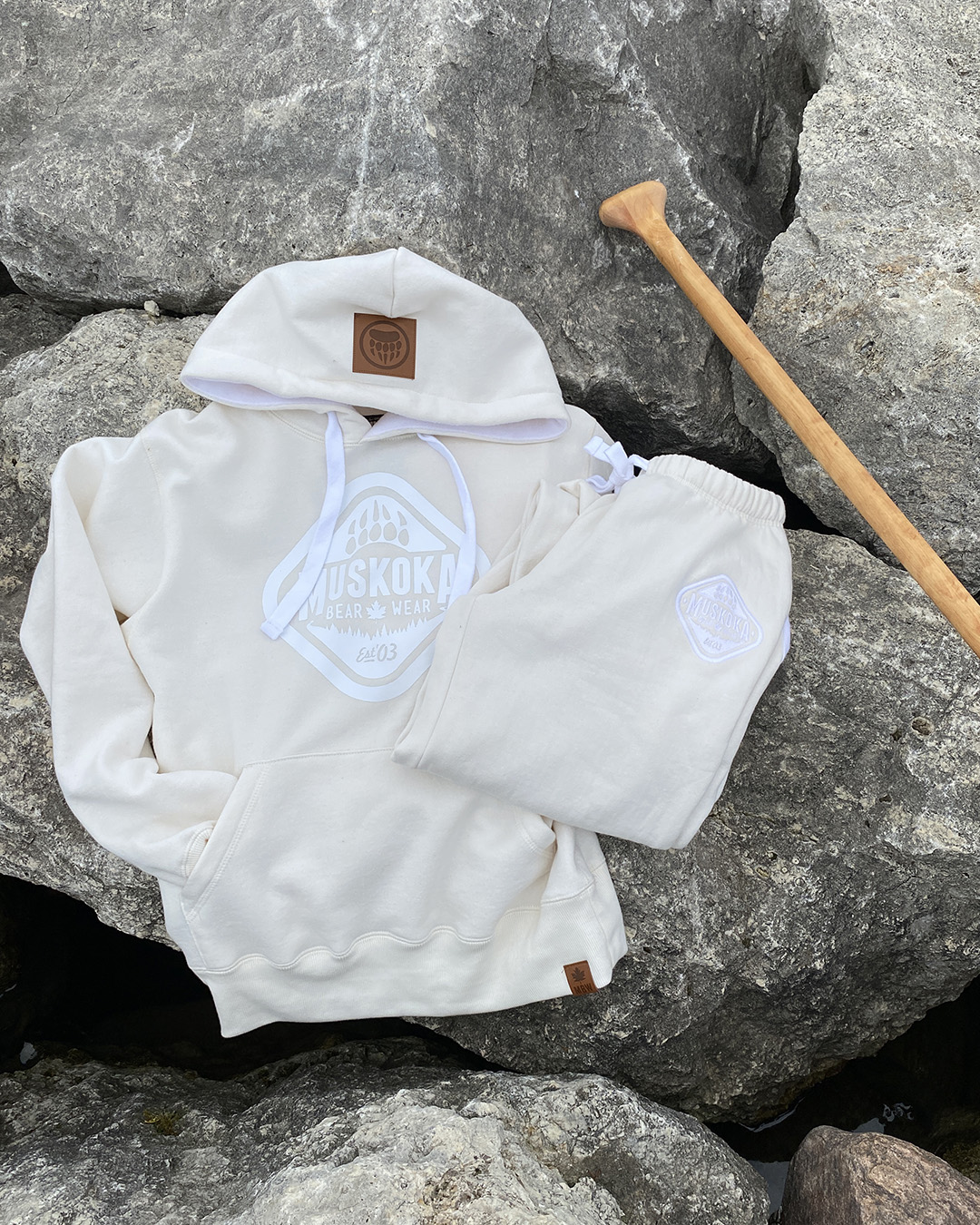 Aerial shot of Ivory Hoody and Ivory sweatpants laying on a rock with a wooden paddle peeking in to photo.