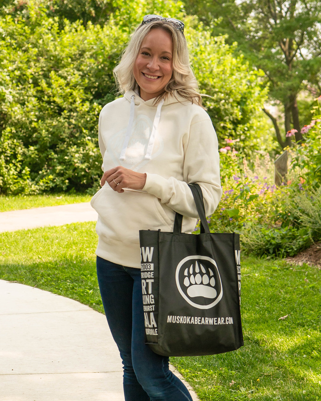 Product Shot of woman wearing a Ivory White Hoody with a white Muskoka Bear Wear logo on the frnot.