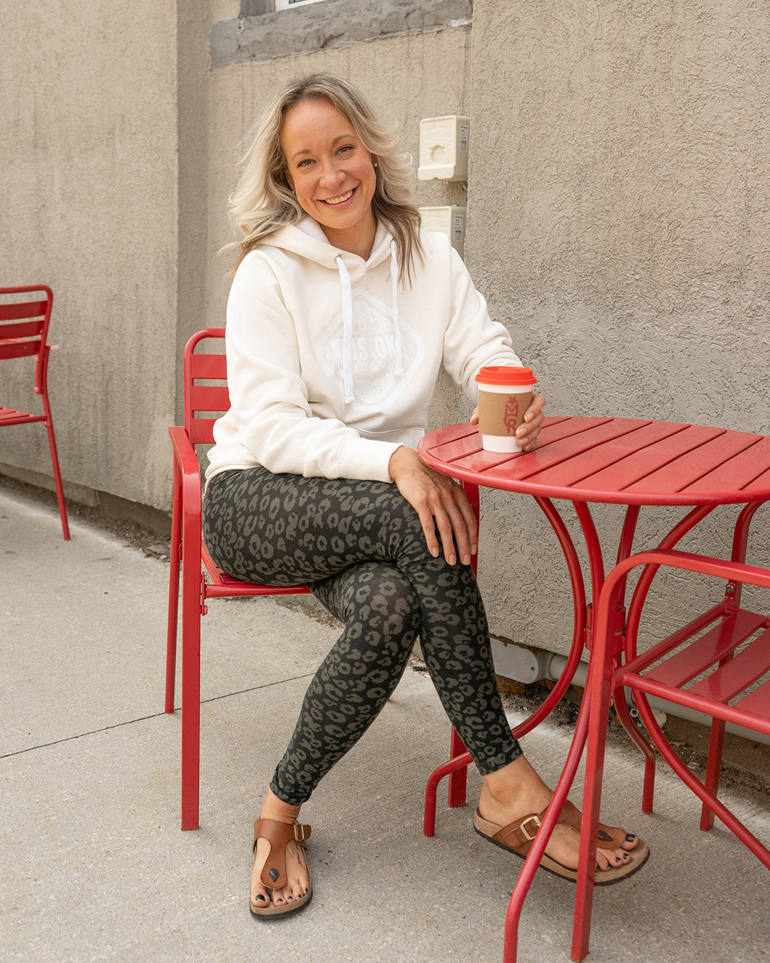 Canadian mom sitting at a cafe table with a coffee wearing a Ivory coloured hoody and printed leggings.