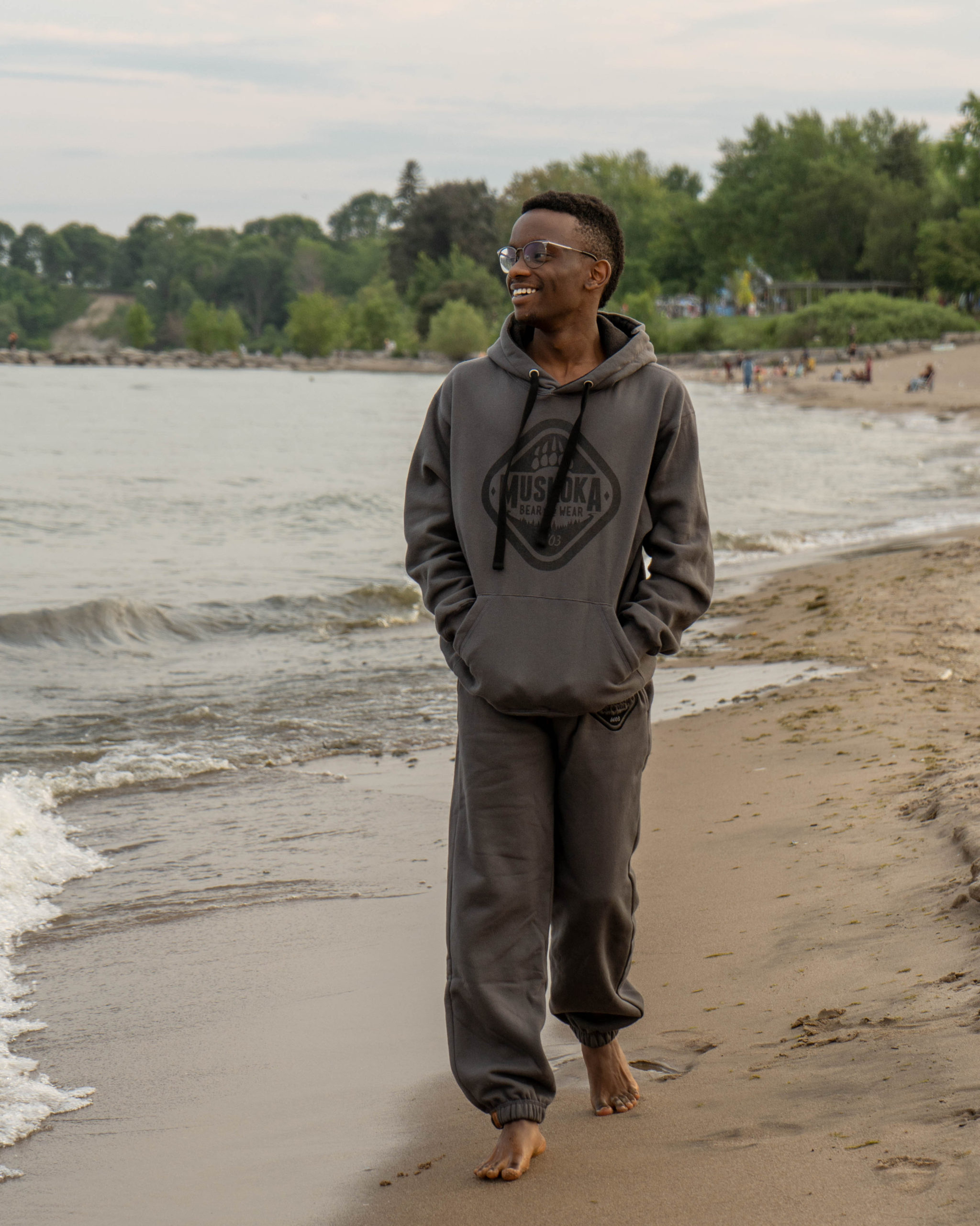 Man walking along beach wearing a matching grey hoody and trackpants